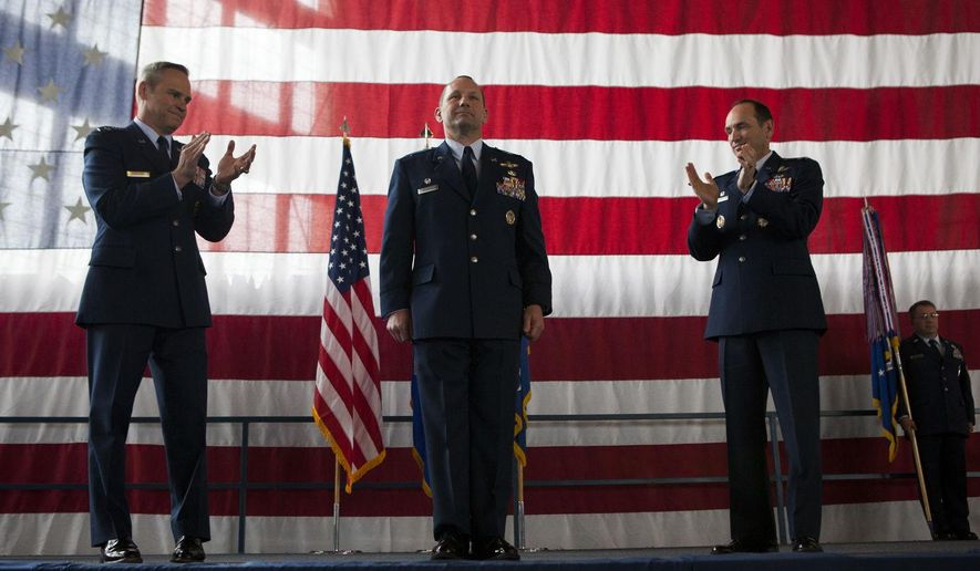 Col. Gentry Boswell, commander of the 28th Bomb Wing, stands at attention as Lt. Gen. Mark Nowland, left, and former commander Col. Kevin Kennedy, right, applaud him at the end of change-of-command ceremony at Ellsworth Air Force Base Thursday, June 4, 2015.  Boswell assumed command as Kennedy prepares to transition from his two years as commander to a new position at the Pentagon.  (Josh Morgan/Rapid City Journal via AP) TV OUT