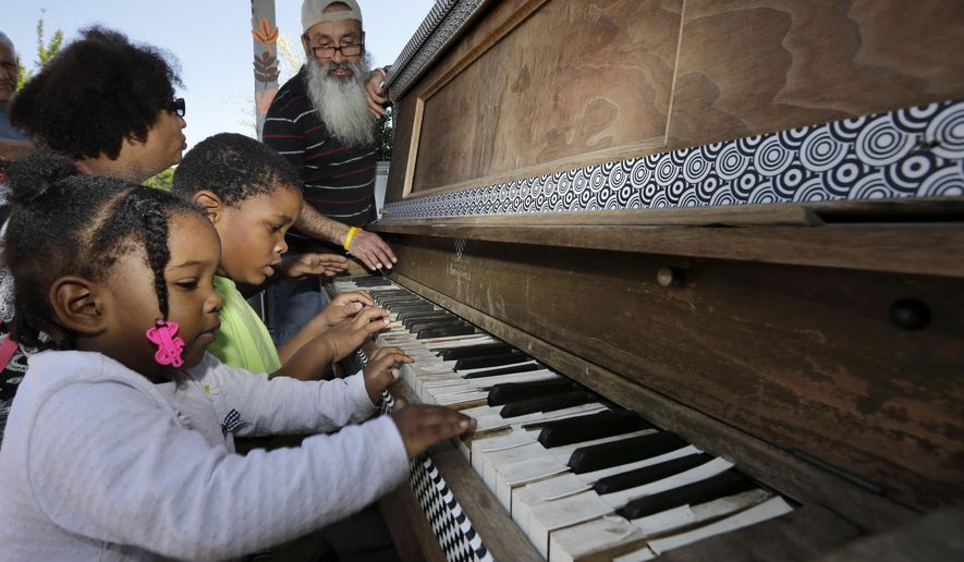In this Tuesday, May 26, 2015, photograph, as Anyalise Boykin, left, 2, and her brother Noah Boykin, 5, play a piano set-up in front of City Hall, their mother Deborah Boykin back left, talks with Reinaldo Suarez, right, in Camden, N.J. The piano is part of a pop-up park that opened last year on Roosevelt Plaza, a new park in front of City Hall in Camden, a city that ranks among the most impoverished and crime-ridden in the country. (AP Photo/Mel Evans)