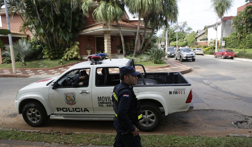 Police patrol outside the home of Nicolas Leoz who's under house arrest in Asuncion, Paraguay, Wednesday, June 3, 2015. Leoz, former Conmebol president and former FIFA executive member, was indicted in a bribery and money-laundering scheme in a FIFA investigation. Leoz has said he'll fight a U.S. extradition order. (AP Photo/Jorge Saenz)