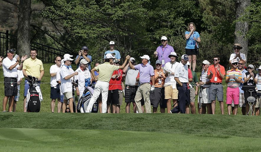 Jason Dufner, center right, celebrates with Kevin Na, after Dufner hit a hole-in-one on the 16th hole during the second round of the Memorial golf tournament, Friday, June 5, 2015, in Dublin, Ohio. (AP Photo/Darron Cummings)