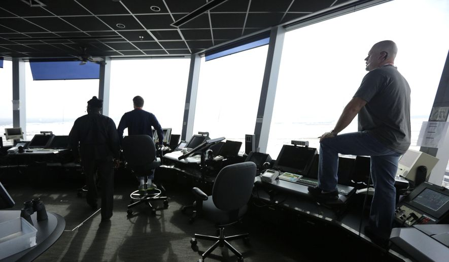 In this Wednesday, Feb. 11, 2015, photo, air traffic controllers monitor traffic in the control tower at O'Hare International Airport in Chicago. (AP Photo/M. Spencer Green)