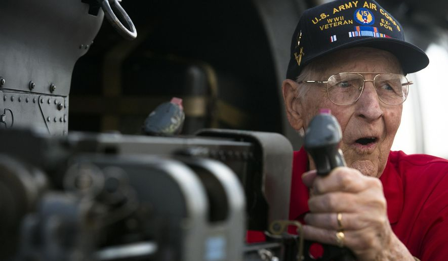 Jim Kirk, a World War II veteran and B-17G ball turret gunner, reacts to holding a 50-cal. machine gun during the Gathering of Eagles event on Friday, June 5, 2015, at Maxwell Air Force Base in Montgomery, Ala. (Albert Cesare/The Montgomery Advertiser via AP)