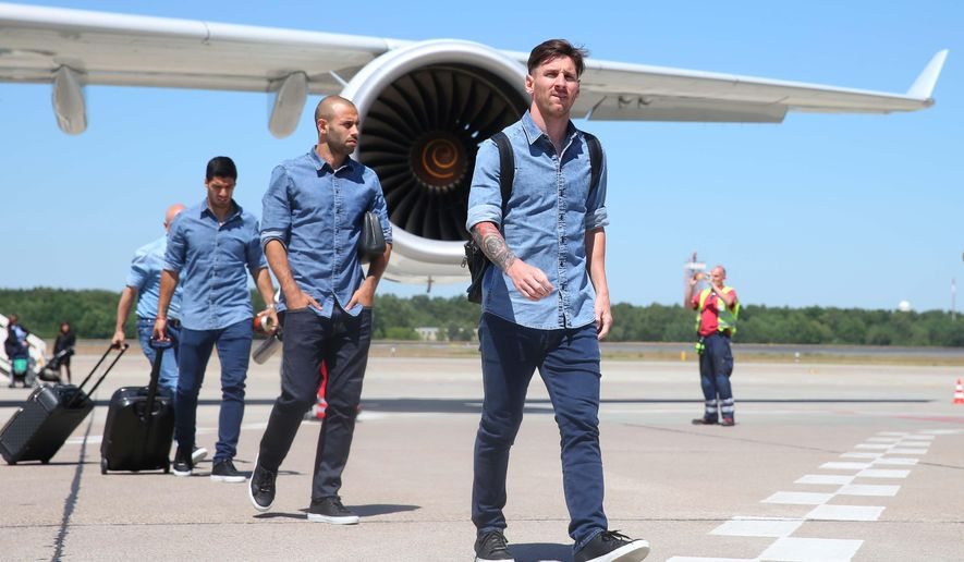 In this image provided by UEFA Barcelona's Lionel Messi, right, Javier Mascherano and Luis Suarez arrive at Tegel Airport in Berlin  Friday, June 5, 2015 on the eve of the soccer Champions League final between Juventus Turin and FC Barcelona on Saturday. (Alexander Hassenstein/UEFA via AP)