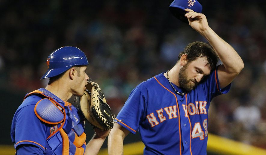 New York Mets' Anthony Recker, left, visits pitcher Jonathon Niese, right, at the mound after Niese's wild throw allowed a Arizona Diamondbacks runner to advance to second base during the third inning of a baseball game Friday, June 5, 2015, in Phoenix. (AP Photo/Ross D. Franklin)