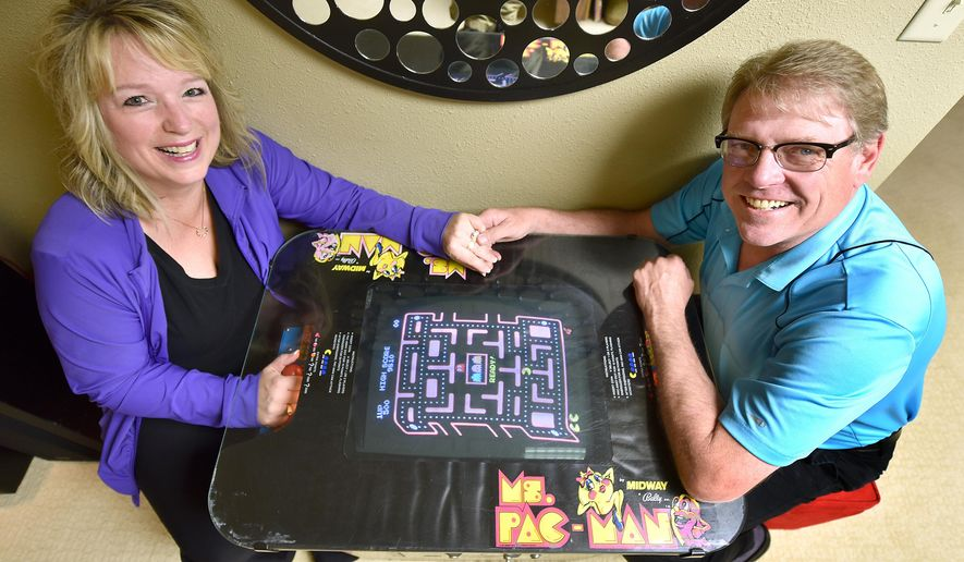 FOR RELEASE SATURDAY, JUNE 6, 2015, AT 12:01 A.M. CDT. - In this photo taken on Monday, June 1, 2015, Kelli, left, and Joe Tuttle play their vintage Ms. Pac-Man cocktail table video game in their Sioux City, Iowa, home. The two were high school sweethearts who used to play Pac-Man against each other when they were kids. This week marks the 35th anniversary of the Pac-Man video game. (Tim Hynds/The Sioux City Journal via AP)
