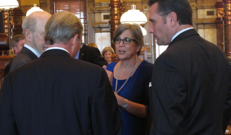 Kansas Senate President Susan Wagle, center, R-Wichita, with Sen. Ty Materson, right, R-Andover, listening, consults with other legislators during a break in the chamber's work, Saturday, June 6, 2015, at the Statehouse in Topeka, Kan. An impasse over budget and tax issues threatened to force furloughs of state workers, but lawmakers averted it by passing a special measure. (AP Photo/John Hanna)