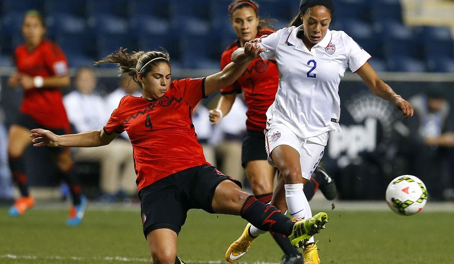 FILE - In this Oct. 24, 2014, file photo, Mexico defender Alina Garciamendez (4) makes a slide tackle on a ball controlled by United States forward Sydney Leroux (2) in the first half of a CONCACAF semifinal soccer match in Chester, Pa. Leroux is a native of British Columbia and even played in the Canadian national team system. But at 15, and holding dual citizenship, she decided to move south in hopes of grabbing the attention of U.S. Soccer. Now Leroux is preparing to represent the United States in the Women's World Cup, in her native Canada. (AP Photo/Rich Schultz, File)