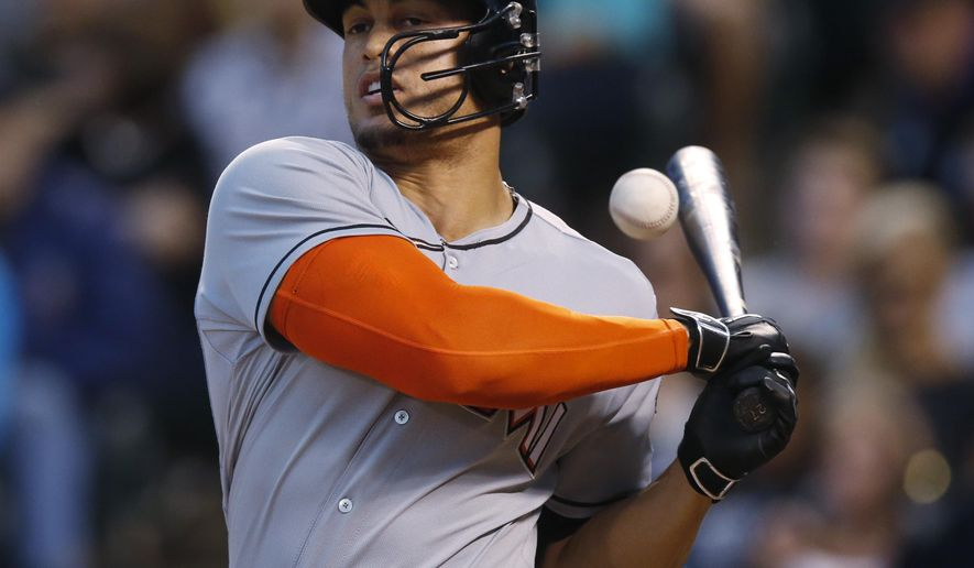 Miami Marlins' Giancarlo Stanton has the ball that he fouled bounce off his bat as he follows through with his swing on a pitch from Colorado Rockies startier Eddie Butler in the fifth inning of a baseball game Friday, June 5, 2015, in Denver. (AP Photo/David Zalubowski)