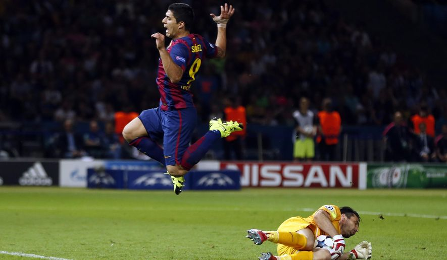 Barcelona's Luis Suarez jumps over Juventus goalkeeper Gianluigi Buffon during the Champions League final soccer match between Juventus Turin and FC Barcelona at the Olympic stadium in Berlin Saturday, June 6, 2015. (AP Photo/Michael Probst)