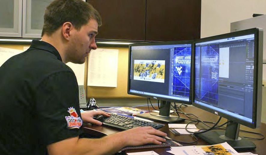 ADVANCE FOR SUNDAY JUNE 7 AND THEREAFTER This Wednesday may 20, 2015 image shows Doug Cross working on a graphic display for the WVU football program at West Virginia University in Morgantown, W.Va. Cross, entering his fourth year as an in-house contractor, helps oversee videos and graphics for the Mountaineers. (Ed Owens/Dominion Post via AP)