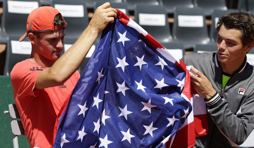 Tommy Paul of the U.S., left, holds the American after winning the boys final match of the French Open tennis tournament against Taylor Harry Fritz of the U.S., right, in three sets 7-6, 2-6, 6-2, at the Roland Garros stadium, in Paris, France, Saturday, June 6, 2015. (AP Photo/Thibault Camus)