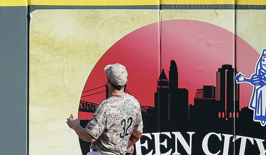 A spectator catches a grand slam hit by San Diego Padres' Yonder Alonso as Cincinnati Reds right fielder Jay Bruce (32) watches in the seventh inning of a baseball game, Saturday, June 6, 2015, in Cincinnati. (AP Photo/John Minchillo)