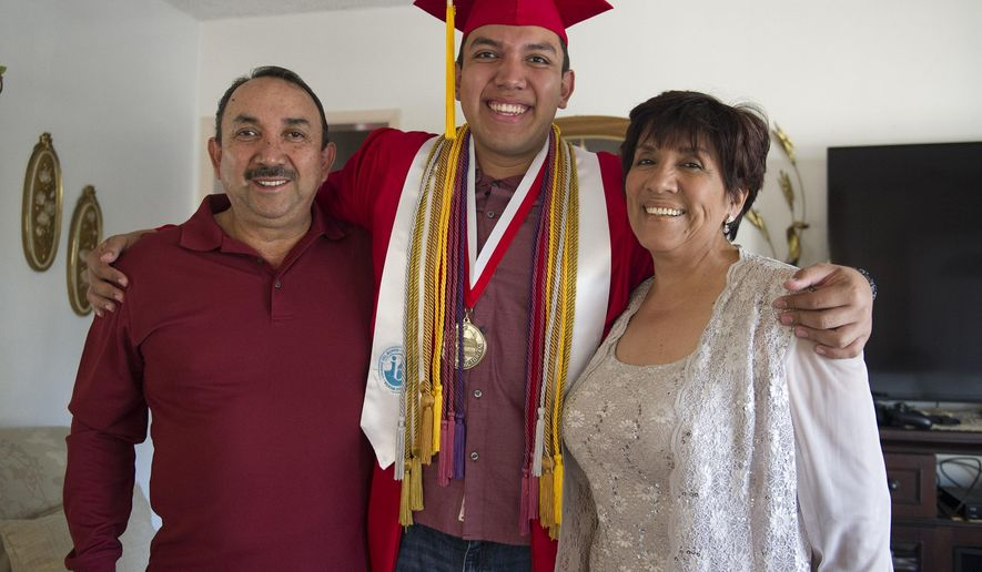 In this May 28, 2015 photo, Fernando Rojas, a senior at Fullerton High School, stands with his parents, Raul Rojas and Maria in Fullerton, Calif. Rojas, the son of Mexican immigrants, was accepted into all eight Ivy League schools. He is planning on attending Yale University in the fall. (Rose Palmisano/The Orange County Register via AP)