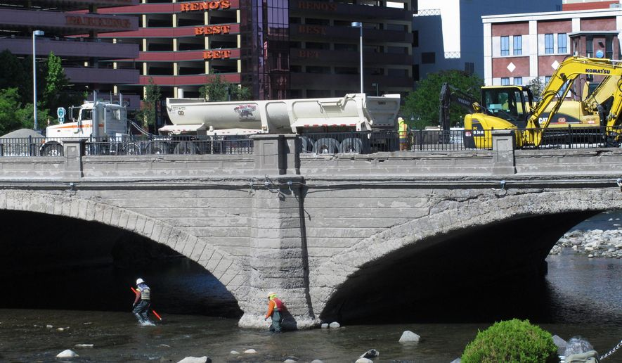 This June 2, 2015 photo shows crews work on top of the Virginia Street Bridge in downtown Reno, Nev. and in the Truckee River below in preparation for demolition of the bridge that was built in 1905. It's being replaced by a modern span as part of a major flood control project and is expected to open in May 2016. (AP Photo/Scott Sonner)
