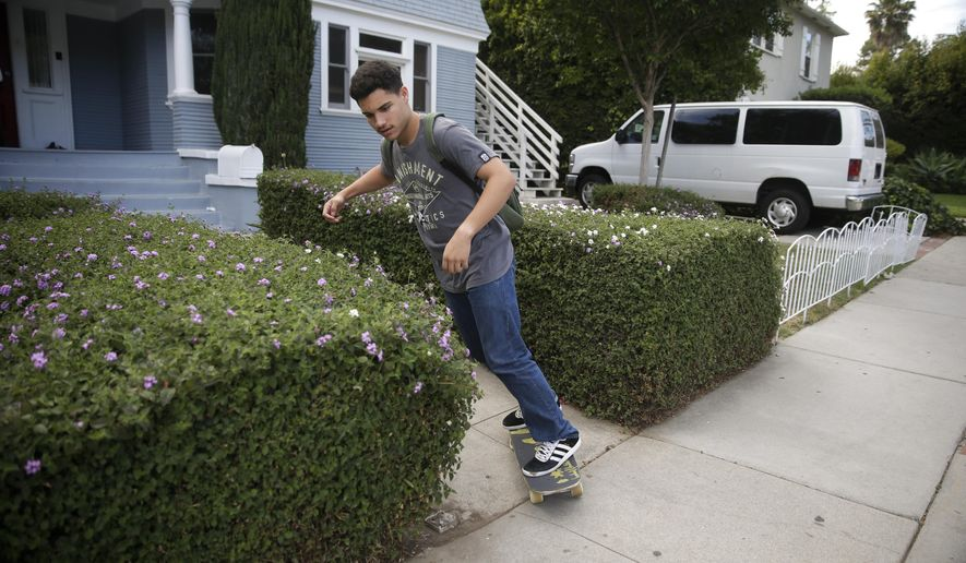 In this Friday, May 1, 2015 photo, Darius Lane rides his skateboard from Beachwood House in Los Angeles to work at a part-time job at a souvenir shop on Hollywood Boulevard. Lane, 17, is a resident at the group home for foster kids without a home. Nationwide, more than 400,000 children are in the foster care system.  (AP Photo/Jae C. Hong)