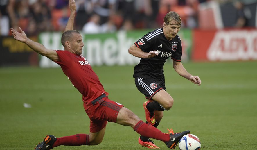 D.C. United forward Chris Rolfe, right, battles for the ball against Toronto FC midfielder Benoit Cheyrou, left, during the first half of an MLS soccer game, Saturday, June 6, 2015, in Washington. (AP Photo/Nick Wass)