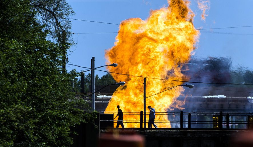 Two people walk along a railroad bridge as flames soar from a gas leak explosion that ignited at about 1 p.m. on Saturday, June 6, 2015 on Dort Highway in Flint, Mich. A portion of Dort Highway between Lapeer Road and Court Street was shut down for the afternoon by Flint Police for safety precaution. Two motorists were injured, and received burn injuries in the explosion. Both were transported to Hurley Medical Center and are listed in non-critical condition. (Jake May/The Flint Journal-MLive.com via AP) LOCAL TELEVISION OUT; LOCAL INTERNET OUT