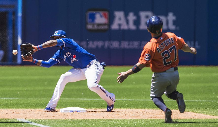 Toronto Blue Jays shortstop Jose Reyes prepares to tag Houston Astros' Jose Altuve as he's picked off stealing second base during the third inning of a baseball game, Saturday, June 6, 2015 in Toronto. (Aaron Vincent Elkaim/The Canadian Press via AP) MANDATORY CREDIT