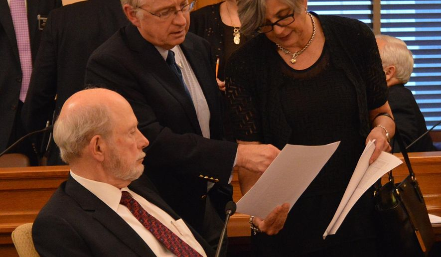 Gordon Self, center, the director of the Kansas Legislature's bill-drafting staff of attorneys, confers with Senate Assessment and Taxation Committee Chairman Les Donovan, left, and Senate President Susan Wagle, right, both R-Wichita, during a break in negotiations with the House on tax issues, Friday, June 5, 2015, at the Statehouse in Topeka, Kan. Legislators inability to pass a tax plan to balance the state budget has prompted state agencies to issue furlough notices to thousands of workers. (AP Photo/Nicholas Clayton)