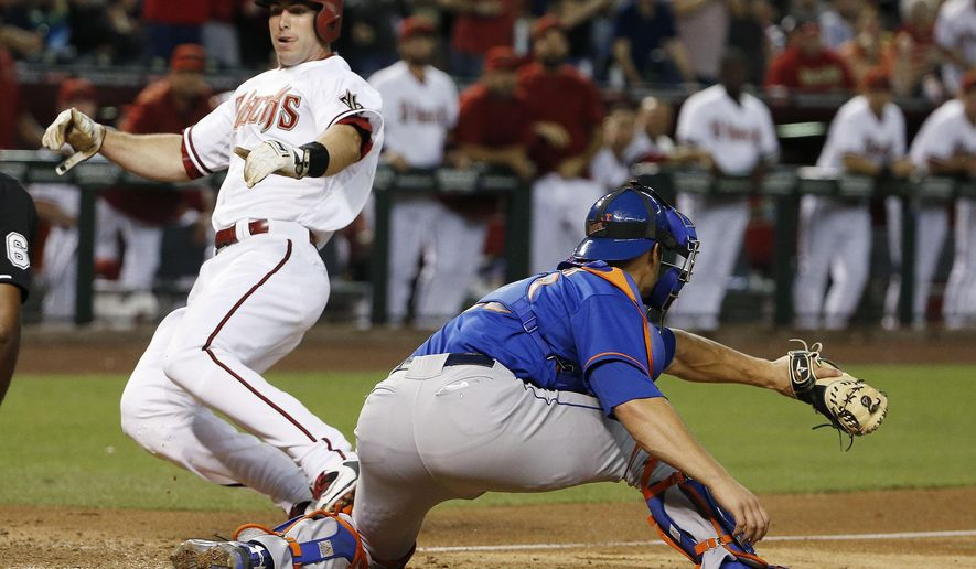 Arizona Diamondbacks' Paul Goldschmidt, left, goes into his slide to score a run ahead of the tag by New York Mets' Anthony Recker, right, during the sixth inning of a baseball game Friday, June 5, 2015, in Phoenix. (AP Photo/Ross D. Franklin)