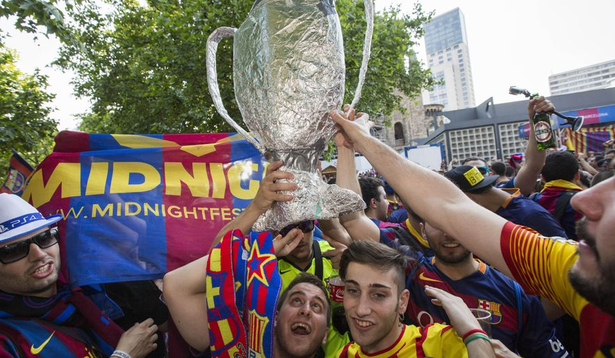 Spanish soccer fans of FC Barcelona celebrate with a self-made trophy before the soccer Champions League final between Juventus Turin and FC Barcelona in Berlin, Germany, Saturday, June 6, 2015. (AP Photo/Gero Breloer)