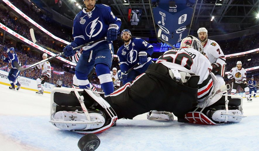 Tampa Bay Lightning right wing J.T. Brown, left, watches as Cedric Paquette's shot goes by Chicago Blackhawks goalie Corey Crawford during the first period in Game 2 of the NHL hockey Stanley Cup Final in Tampa, Fla., Saturday, June 6, 2015. (Bruce Bennett/Pool Photo via AP)