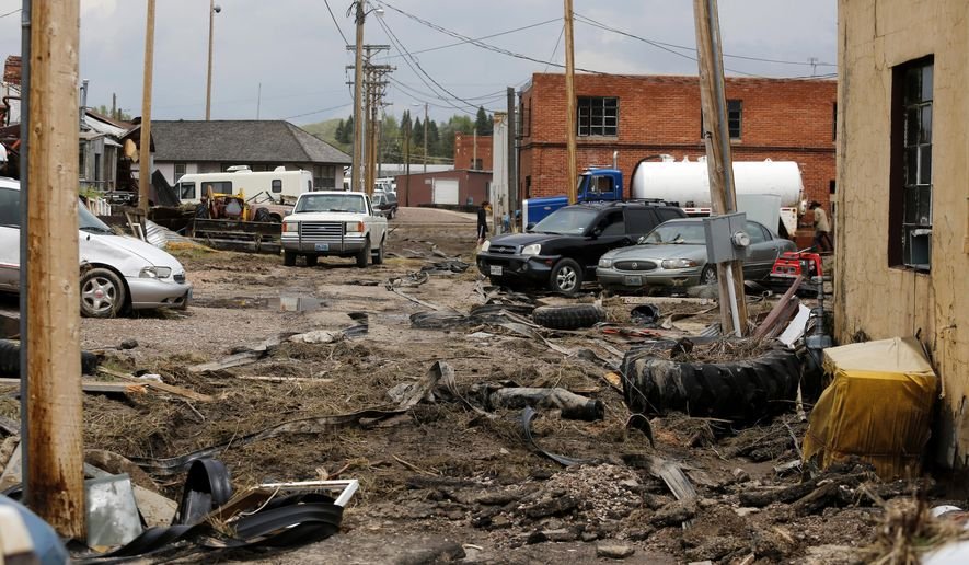 Mud and debris cover a side street Friday, June 5, 2015 in Lusk. Parts of Lusk, Wyo, Manville and other areas of Niobrara County were flooded early Thursday when intense rains caused the Niobrara River to overflow its banks. The Red Cross said 11 homes were destroyed by the flash flood, which also collapsed a U.S. 85 overpass and washed out other sections of highway. (Alan Rogers/The Casper Star-Tribune via AP)