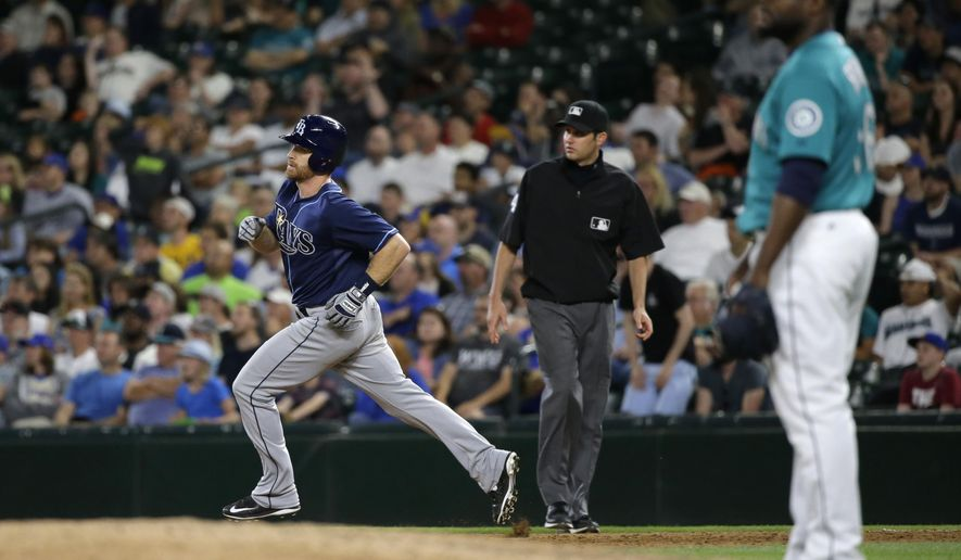 Tampa Bay Rays' Logan Forsythe, left, rounds first base after he hit a solo home run off Seattle Mariners closing pitcher Fernando Rodney, right, in the ninth inning of a baseball game, Friday, June 5, 2015, in Seattle. It was the first run scored by either team in the game. (AP Photo/Ted S. Warren)