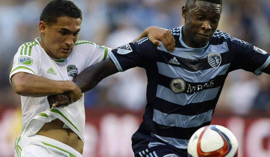 Seattle Sounders midfielder Cristian Roldan, left, defends against Sporting KC defender Jalil Anibaba, right, during the first half of an MLS soccer match in Kansas City, Kan., Saturday, June 6, 2015. (AP Photo/Orlin Wagner)