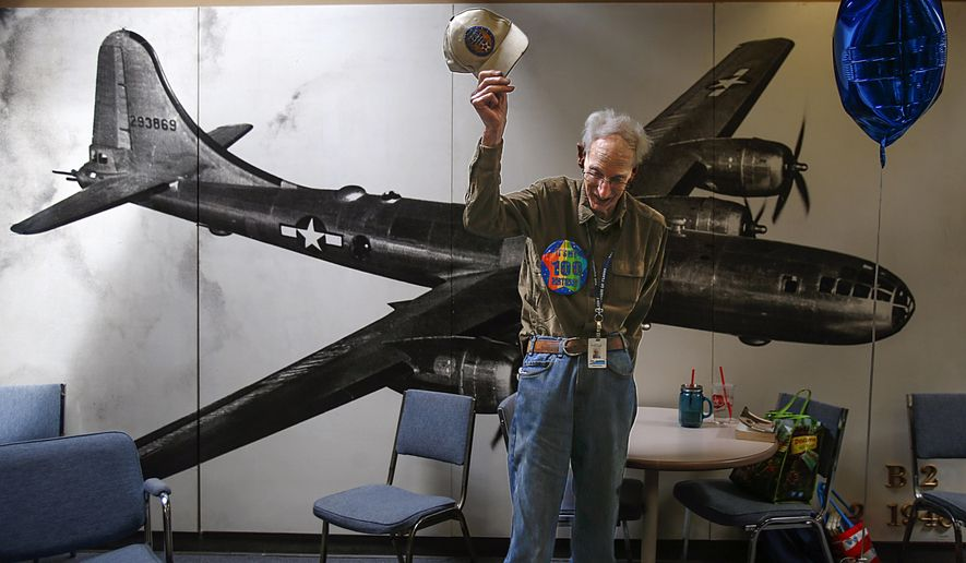 Jimmy Jackson tips his hat in front of a picture of a B29 Bomber, the aircraft he worked on during the World War II, during a birthday party for the 100-year-old at the Museum of Flight Restoration Center at Paine Field, in Everett, June 3, 2015. The picture graces one wall in the room at the restoration center where the birthday party was held. Jackson still volunteers at least two days a week at the Museum of Flight Restoration Center. Ask him, though, and there's nothing remarkable about him staying busy transforming pieces of raw metal into airplane parts. He's just part of the crew keeping the facility running. (Dan Bates, /The Herald via AP)