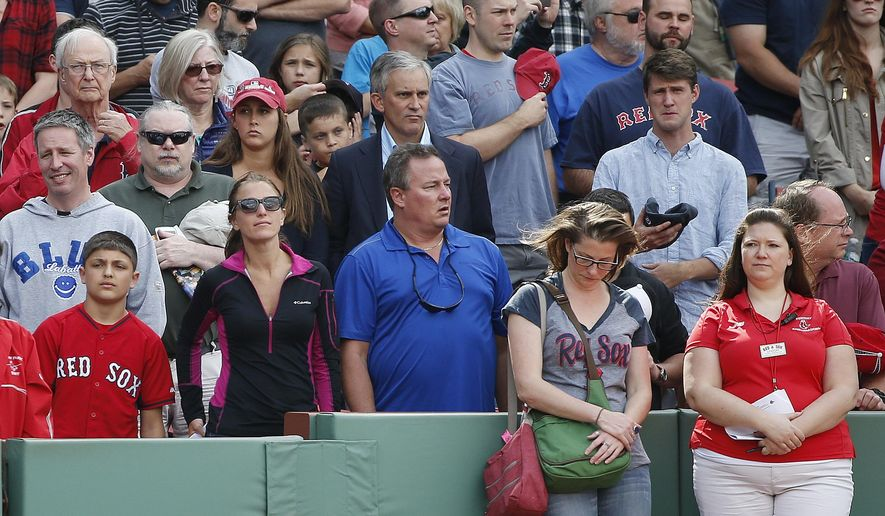 Fans observe a moment of silence before a baseball game between the Boston Red Sox and the Oakland Athletics, at Fenway Park in Boston, Saturday, June 6, 2015, in the area of the stands where a woman was hit and seriously injured by a broken bat during Friday's game. (AP Photo/Michael Dwyer)