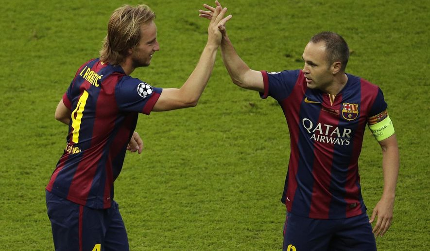 Barcelona's Ivan Rakitic, celebrates with Andres Iniesta scoring the opening goal during the Champions League final soccer match between Juventus Turin and FC Barcelona at the Olympic stadium in Berlin Saturday, June 6, 2015. (AP Photo/Michael Sohn)