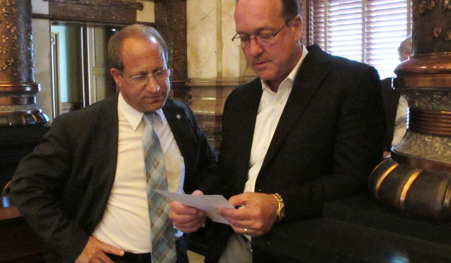 Kansas state Sens. Forrest Knox, left, R-Altoona, and Jeff Longbine, right, R-Emporia, confer during the Senate's debate over a plan for raising taxes to close a projected state budget shortfall, Sunday, June 7, 2015, at the Statehouse in Topeka, Kan. Among other things, the plan raises business taxes by $24 million during the fiscal year beginning July 1, the top amount Gov. Sam Brownback will accept. (AP Photo/John Hanna)