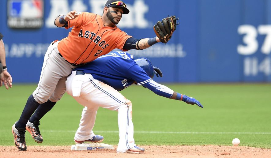 Toronto Blue Jays' Jose Reyes stands at second base as Houston Astros shortstop Jonathan Villar runs into him and misplays a pop fly during ninth inning of a baseball game against Sunday, June 7, 2015, in Toronto. The Blue Jays won 7-6. (Frank Gunn/The Canadian Press via AP) MANDATORY CREDIT