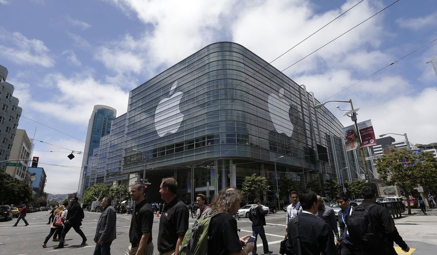 FILE - In this June 2, 2014 file photo, pedestrians cross the street in front of the Moscone Center, which is hosting the Apple Worldwide Developers Conference, in San Francisco. Apple is expected to announce its new paid streaming-music service at its annual conference for software developers, which kicks off Monday, June 8, 2015. (AP Photo/Jeff Chiu, File)