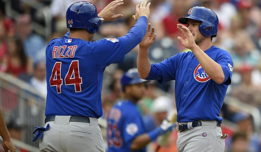 Chicago Cubs' Kris Bryant, right, reacts with teammate Anthony Rizzo (44) after they scored on a hit by Chris Coghlan during the fifth inning of a baseball game Washington Nationals, Sunday, June 7, 2015, in Washington. (AP Photo/Nick Wass)