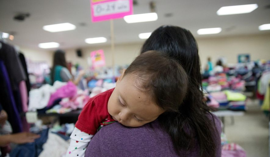 In this April 30, 2015 photo, Gladys Pina, 30, from Honduras holds her 8-month old baby girl at a respite center run by Catholic Charities in McAllen, Texas. She was among nearly two-dozen immigrant mothers who arrived at the center after being released by Border Patrol. Rather than getting locked up in a family detention facility, some families are released by Border Patrol with notices to appear in immigration court. (AP Photo/Seth Robbins)