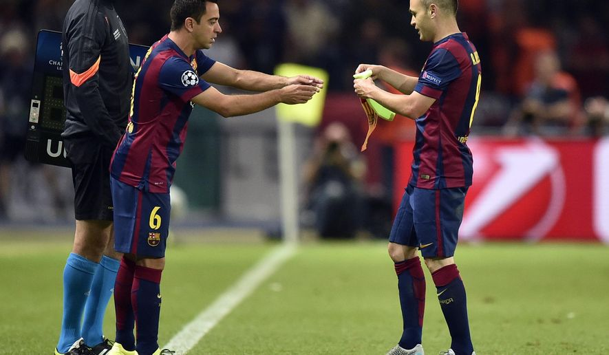 Barcelona's Andres Iniesta, right, gives the captain's armband to his teammate Xavi Hernandez as he is substituted by him during the Champions League final soccer match between Juventus Turin and FC Barcelona at the Olympic stadium in Berlin Saturday, June 6, 2015. (AP Photo/Martin Meissner)