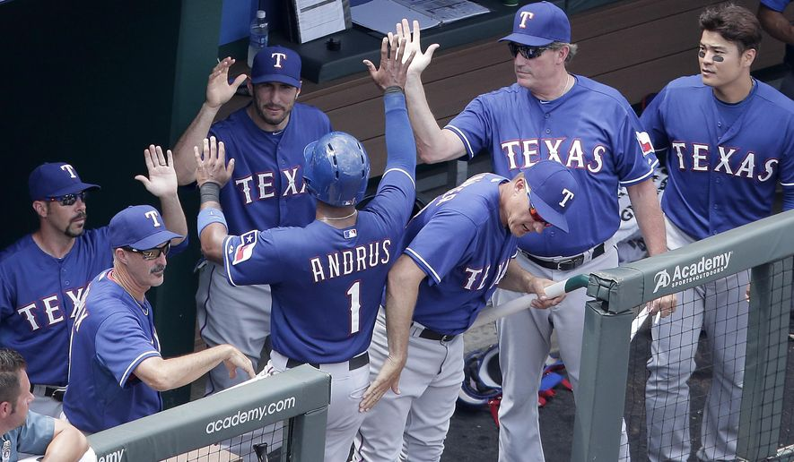 Texas Rangers' Elvis Andrus (1) is welcomed into the dugout after scoring on a ground out hit by Robinson Chirinos during the seventh inning of a baseball game against the Kansas City Royals, Sunday, June 7, 2015, in Kansas City, Mo. (AP Photo/Charlie Riedel)