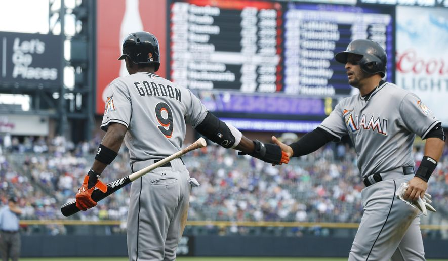 Miami Marlins' Dee Gordon, left, congratulates teammate Martin Prado after they scored on a single by Marcell Ozuna off Colorado Rockies starting pitcher Kyle Kendrick in the first inning of a baseball game, Sunday, June 7, 2015, in Denver. (AP Photo/David Zalubowski)