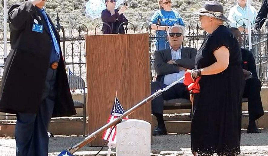 John Riggs of the Sons of Union Veterans of the Civil War, left, and Linda Clements of the Historical Society of Dayton Valley pay their respects to Pvt. Scott Carnal of the 1st Kansas Colored Infantry during a ceremony Sunday, June 7, 2015, at his grave in Dayton, 30 miles south of Reno, Nev. Carnal, a runaway slave who joined the Union Army during the Civil War and lost a leg after being wounded in battle, finally received recognition during a military funeral Sunday, nearly 100 years after he died in Nevada. (Lynne Ballatore/Historical Society of Dayton Valley, via AP)