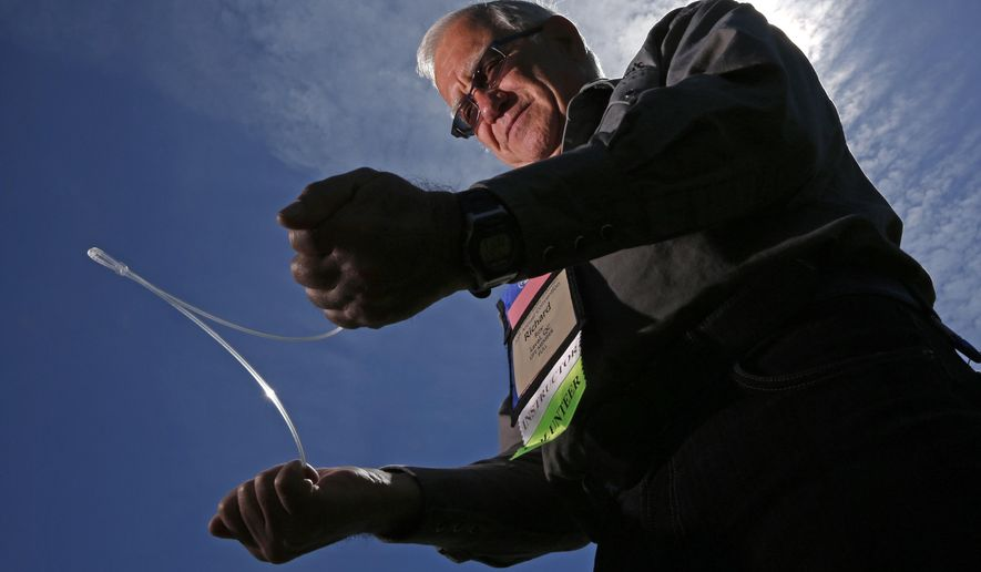 In this Thursday, June 4, 2015 photo, Richard Roy of Laval, Quebec, Canada, demonstrates the use of a Y-rod at the American Society for Dowsing's annual convention in Lyndonville, Vermont. Practitioners of dowsing use metal rods, forked sticks and pendulums and what they say is their subconscious to tap into a universal natural knowledge. (AP Photo/Robert F. Bukaty)