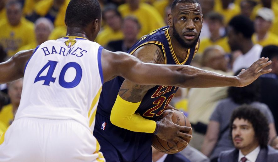 Cleveland Cavaliers forward LeBron James, right, is guarded by Golden State Warriors forward Harrison Barnes (40) during the first half of Game 2 of basketball's NBA Finals in Oakland, Calif., Sunday, June 7, 2015. (AP Photo/Ben Margot)