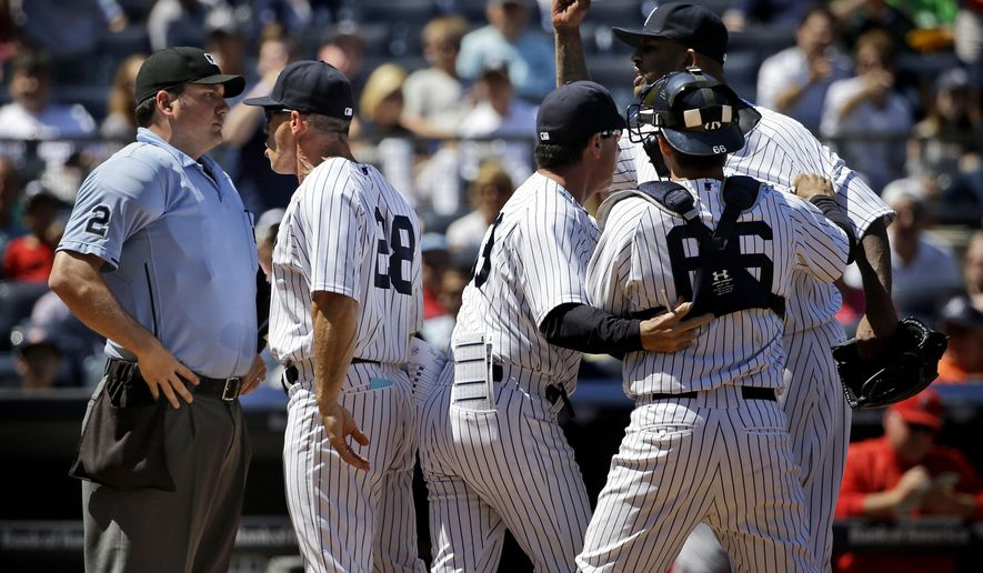 Teammates hold back New York Yankees starting pitcher CC Sabathia, right, as manager Joe Girardi, second from left, argues with umpire Dan Bellino, left, during the sixth inning of a baseball game against the Los Angeles Angels, Sunday, June 7, 2015, in New York. Both Sabathia and Girardi were ejected from the game. (AP Photo/Seth Wenig)