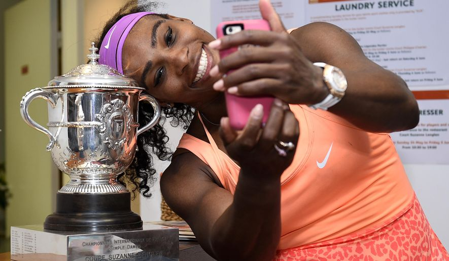 Serena Williams of the U.S. poses for a selfie with the trophy in the cloakroom after winning the French Open Tennis tournament against Lucie Safarova of the Czech Republic, at the Roland Garros stadium in Paris, France, Saturday, June 6, 2015. Williams won 6-3, 6-7, 6-2. (Corinne Dubreuil, FFT, Pool via AP)