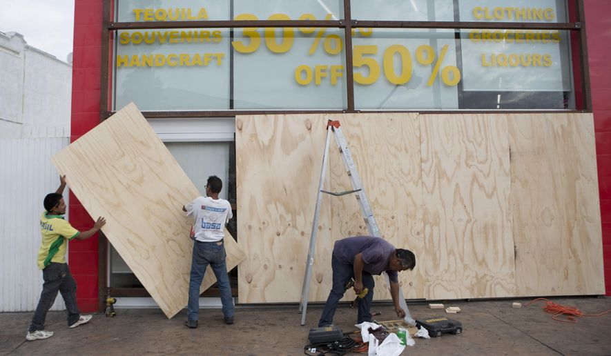 Workers board over store front windows in preparation for Hurricane Blanca, in Cabo San Lucas, Mexico, Sunday June 7, 2015. The unpredictable storm strengthened rapidly to a Category 4 storm on Saturday, but the U.S. National Hurricane Center says it has since weakened to Category 1 with top winds near 90 mph. (AP Photo/Eduardo Verdugo)