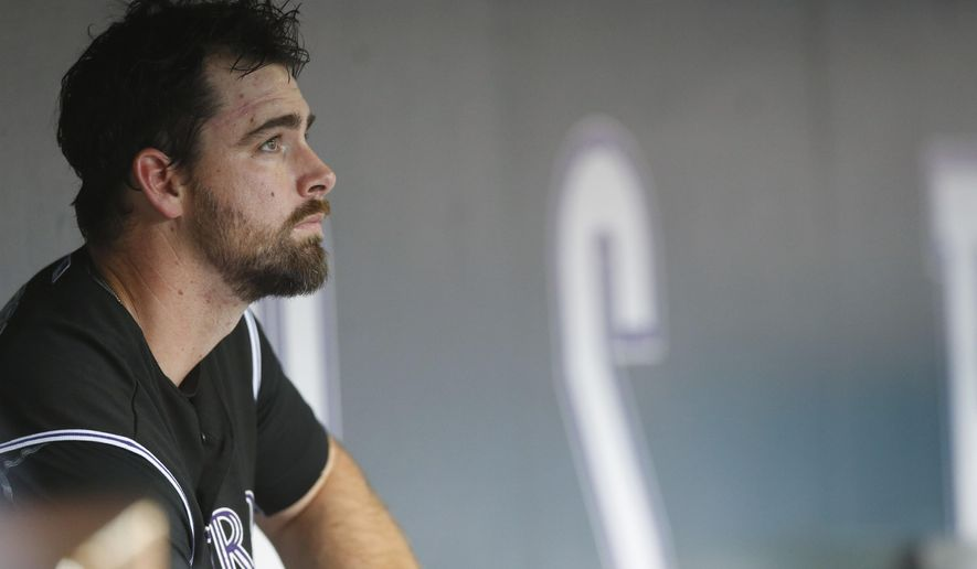 Colorado Rockies relief pitcher Boone Logan sits in the dugout after giving up a solo home run to Miami Marlins' Adeiny Hechavarria in the 10th inning of a baseball game Sunday, June 7, 2015, in Denver. The Marlins won 3-2. (AP Photo/David Zalubowski)