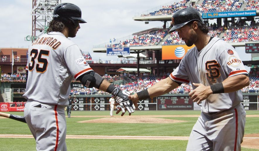 San Francisco Giants' Angel Pagan, right, celebrates his run with Brandon Crawford, left, during the third inning of a baseball game against the Philadelphia Phillies, Sunday, June 7, 2015, in Philadelphia. (AP Photo/Chris Szagola)