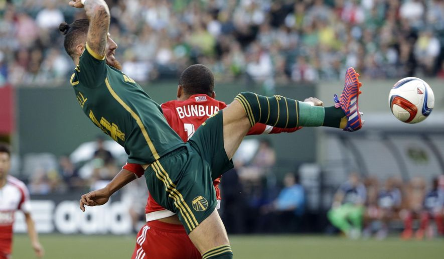 Portland Timbers defender Liam Ridgewell, left, and New England Revolution forward Teal Bunbury battle for the ball during the first half of an MLS soccer game in Portland, Ore., Saturday, June 6, 2015. (AP Photo/Don Ryan)
