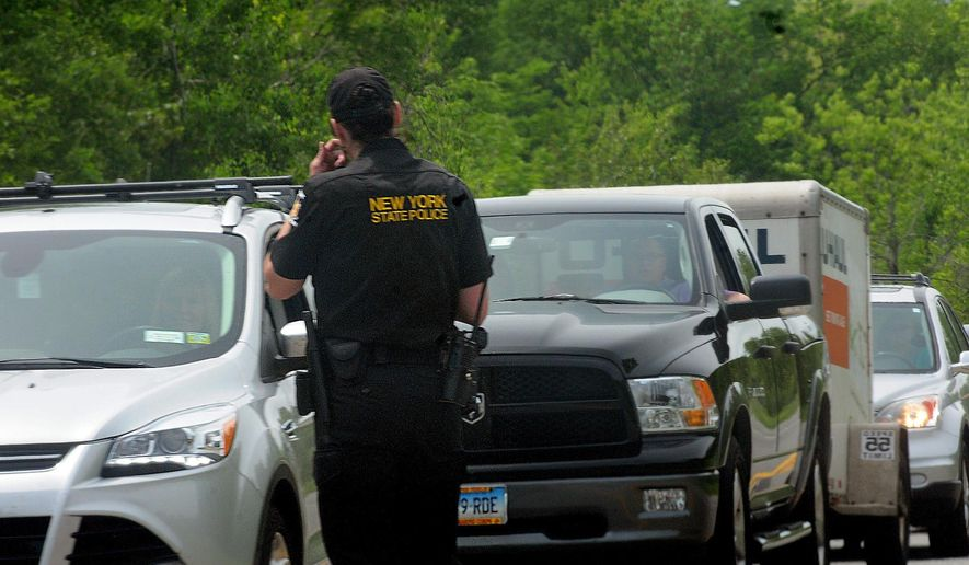 Law enforcement officers search for two escaped prisoners Sunday, June 7, 2015, near Dannemora, N.Y. The two murderers who used power tools to escape from prison must have taken days to cut through steel walls and pipes and break through the bricks at the maximum-security prison, New York Gov. Andrew Cuomo said Sunday. (Rob Fountain/The Press-Republican via AP)